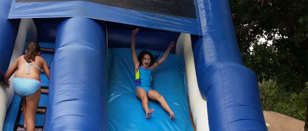 Dolphin waterslide rental wiht girl sliding down in Port Orange Florida
